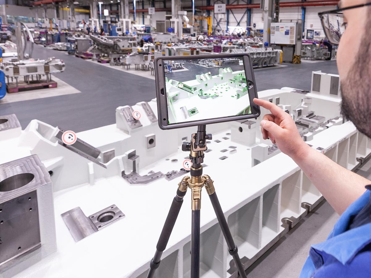 BMW Mitarbeiter nutzt ein auf einem Stativ befestigtes Tablet zum Abgleich von echtem Bauteil mit den zugehörigen Konstruktionsdaten
