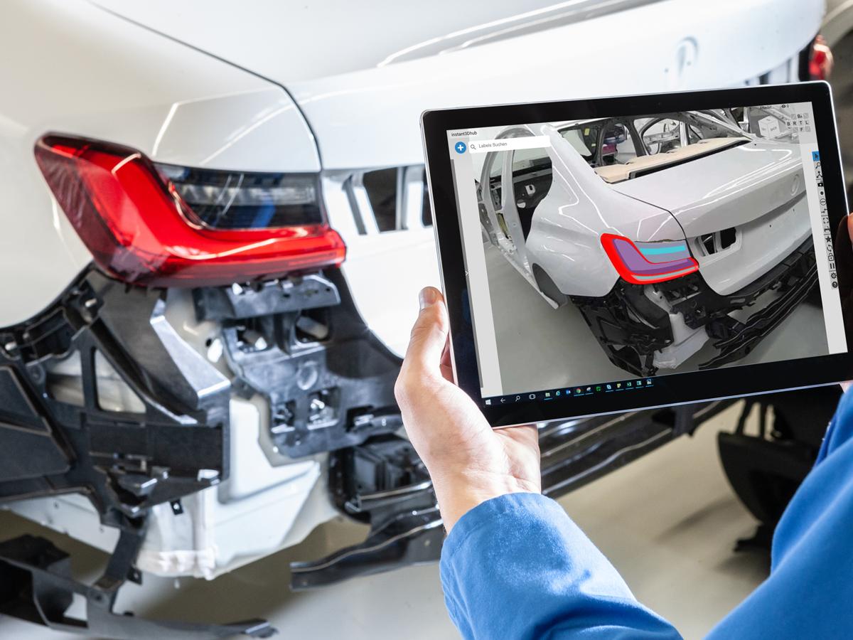 BMW Mitarbeiter hält ein Tablet in der Hand und vergleicht die virtuelle Welt auf dem Display mit der chten Fahrzeugkarosserie