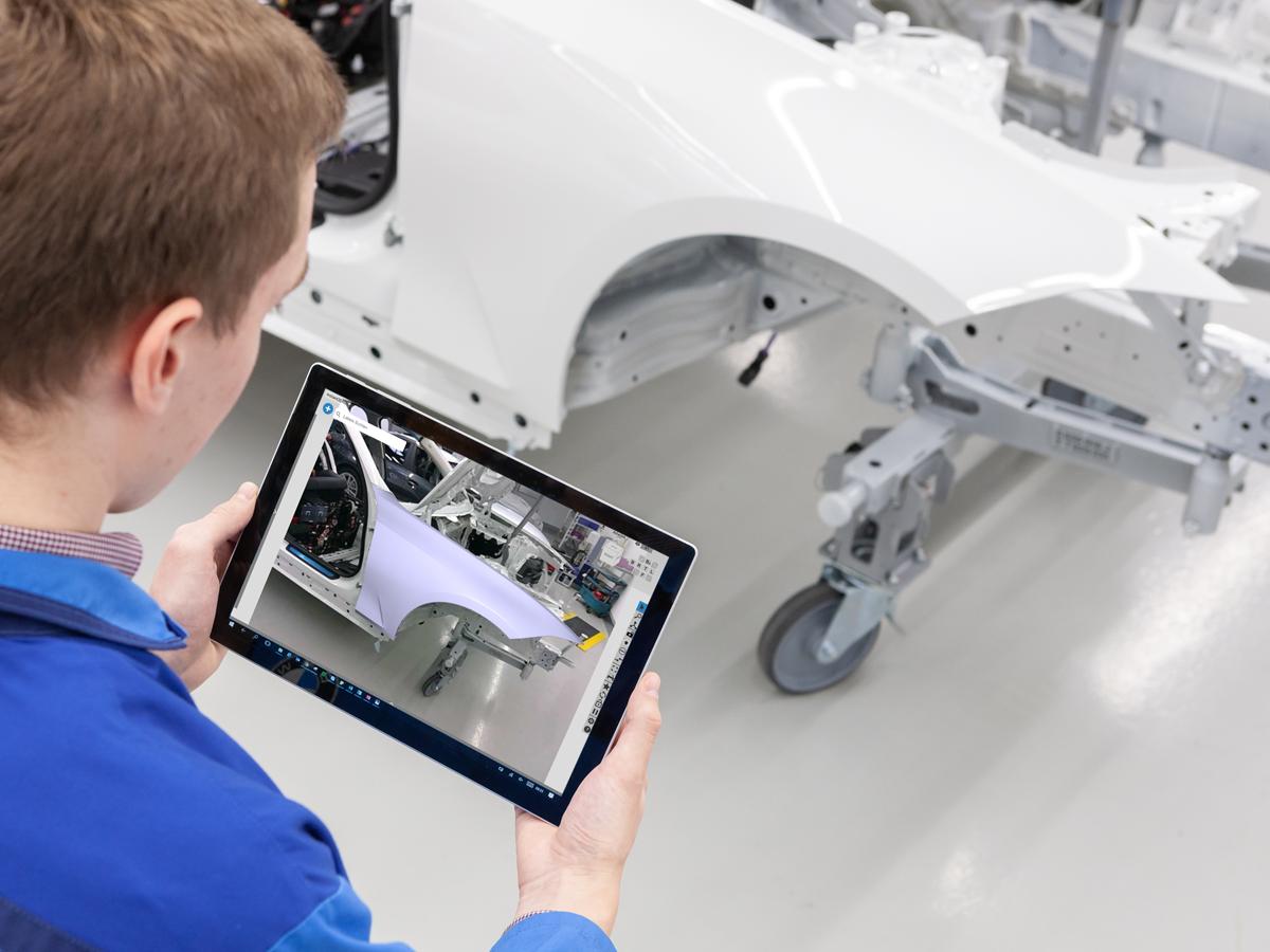 BMW-Mitarbeiter hält Tablet in den Händen und gleicht die reale Welt mit der virtuellen Welt auf dem Display ab